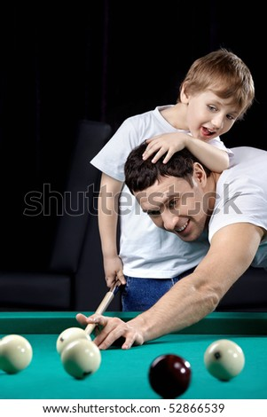 The young man and the little boy play billiards - stock photo