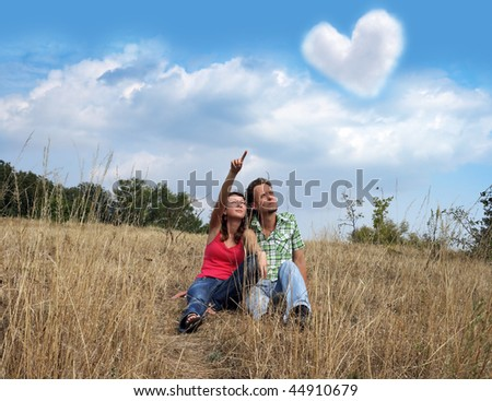 The young man and the woman look upwards at a cloud in the form of heart. The loving couple sits in a dry grass. - stock photo