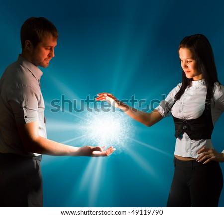 The Young man and young woman keeps in their own hands the shining energy ball. - stock photo