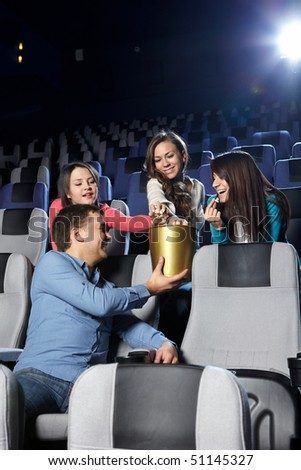 The young man at cinema gives girls pop-corn - stock photo