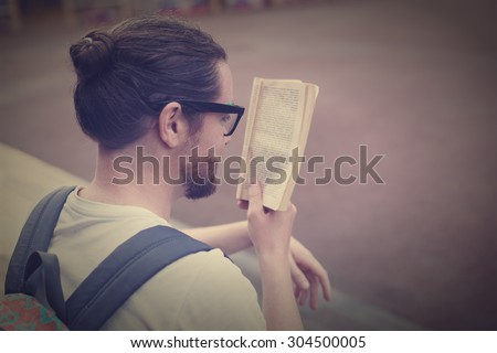 The young man, bearded student sitting on the steps of reading a book or textbook. - stock photo