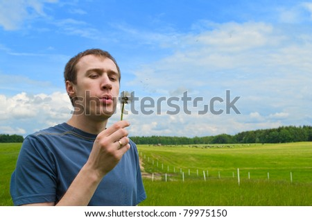 The young man blows on a dandelion on a green meadow - stock photo