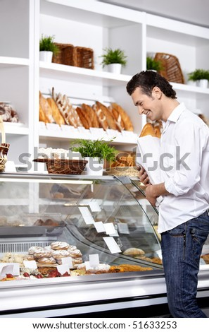 The young man buys bread in shop - stock photo
