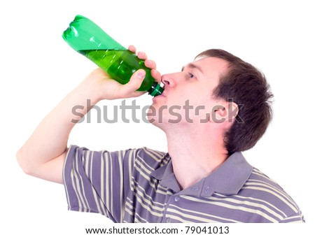 The young man drinks from a green bottle - stock photo