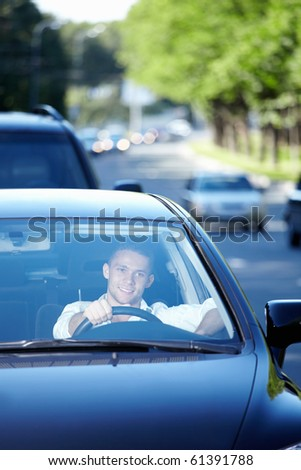 The young man driving a car - stock photo