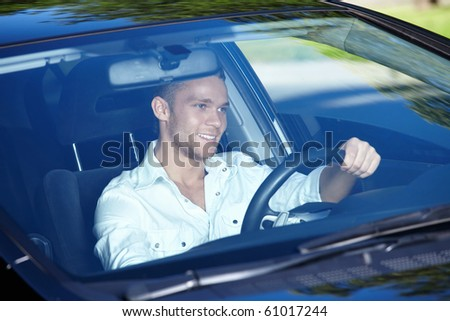 The young man driving a nice car