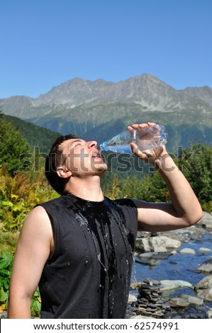 The young man eagerly drinking water from plastic bottles, white mountain river, mountain top - stock photo