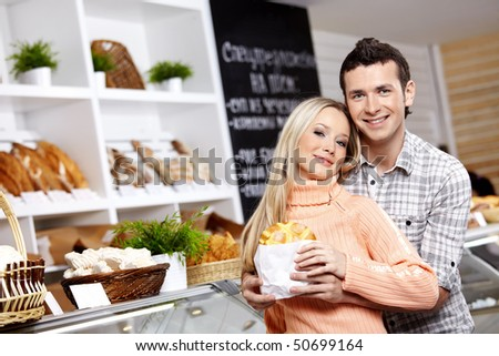 The young man embraces the girl who holds a roll - stock photo