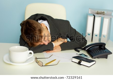 The young man fell asleep on the desktop in the office - stock photo