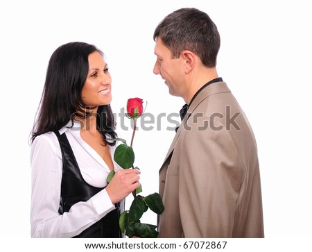The young man gives his girlfriend a rose in honor of Valentine's Day