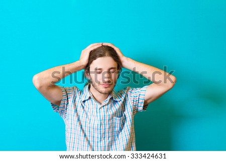 the young man grabbed his head - stock photo