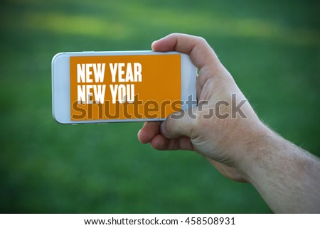 The young man holds the hand New Year New You by smartphone - stock photo