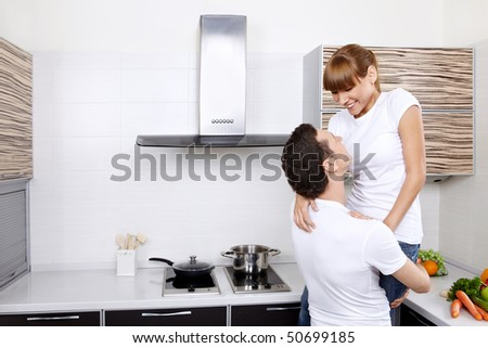 The young man holds the smiling girl at kitchen - stock photo