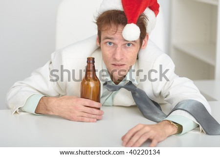 The young man in a Christmas hat at office with a beer bottle