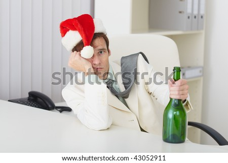The young man in a christmas hat with a bottle sits at a table - stock photo