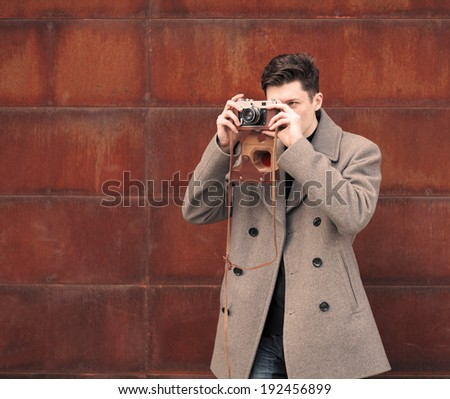 the young man in a coat photographs model the vintage camera at a metal rusty wall - stock photo