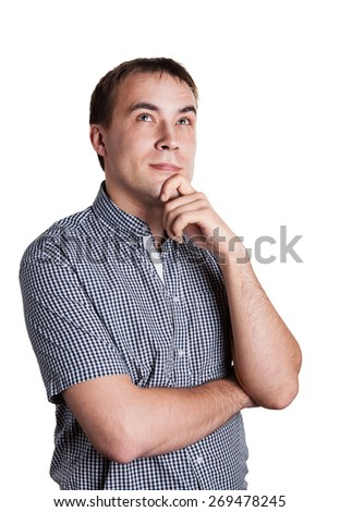 the young man in a plaid shirt thoughtfully looks upward and smiles on isolated white background - stock photo