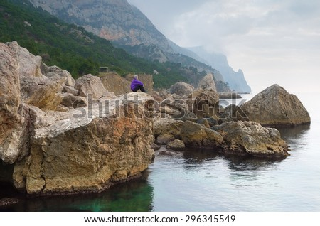 The young man in a purple sweater sitting on a rock. Landscape with sea and rocks. It's a nasty day. Crimea. - stock photo