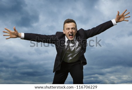 The young man in a suit raises his arms up. . He's looking far. Emotions and movement. - stock photo