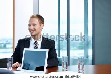 The young man in a suit with the laptop at office - stock photo