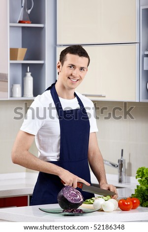 The young man in an apron cuts vegetables on kitchen - stock photo