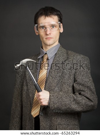 The young man in goggles keeps in readiness a hammer - stock photo