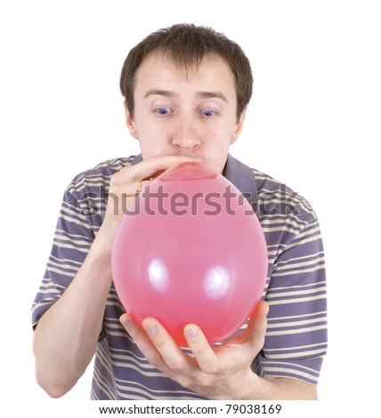 The young man inflates a red balloon - stock photo