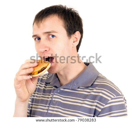 The young man is appetizing eats a hamburger - stock photo