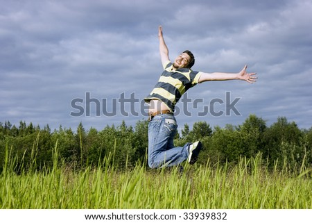 The young man joyfully jumps up in a grass