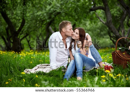 The young man kisses the girl in park - stock photo