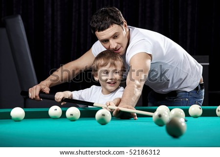 The young man learns the little boy to play billiards - stock photo