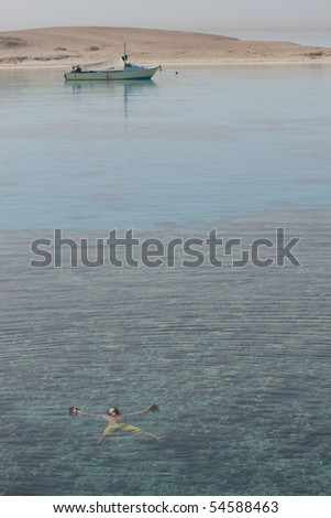 The young man lies on water by the red sea - stock photo