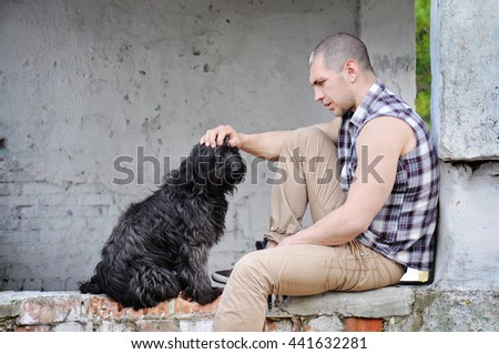The young man looks at a stray shaggy black dog and keeps a hand on the dog's head. Concept home, sad, solitude and thinking. Good space on brick wall. - stock photo