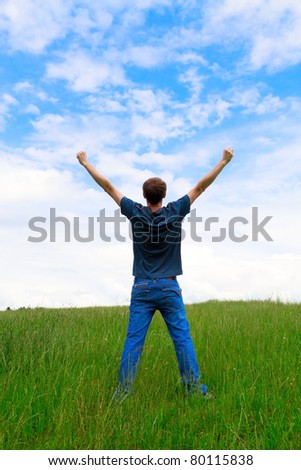 The young man on a meadow having lifted hands upwards - stock photo