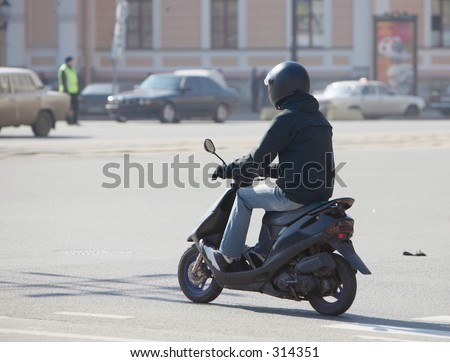 The young man on a motor scooter.