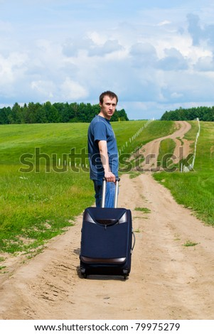 The young man on road in the field with a suitcase - stock photo