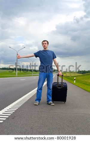 The young man pending on road with a suitcase - stock photo