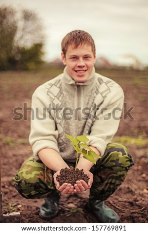 The young man plants a tree. - stock photo