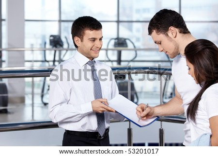The young man signs the document in fitness club - stock photo