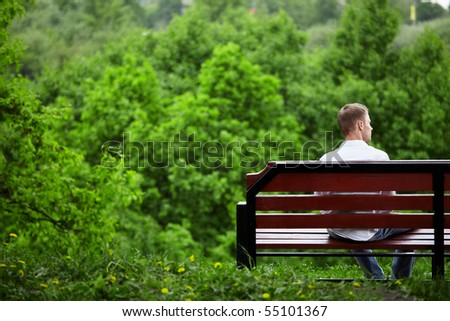 The young man sits one on a bench against green trees - stock photo