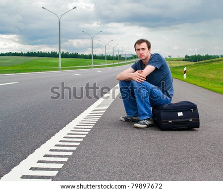 The young man sits pending on road with a suitcase - stock photo