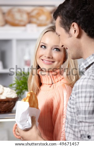 The young man stretches to the girl a roll - stock photo
