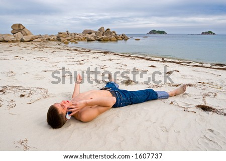 The young man talks on mobile on a deserted beach. - stock photo