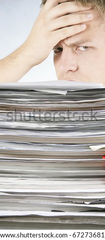 The young man tensely looks at a bale of papers and catalogs - stock photo