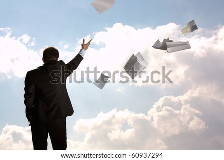 The young man, the businessman, in a dark business suit throws a pile of documents upwards, aside. The beginning of new life. - stock photo