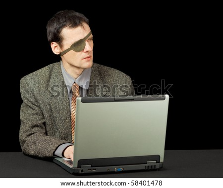 The young man - the computer pirate with the laptop - stock photo