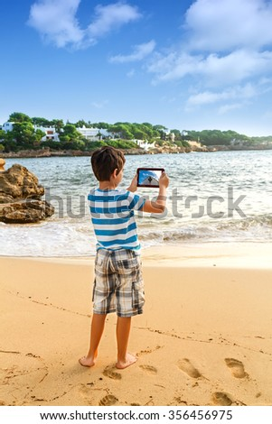 The young man  traveler photographing sea island view with digital tablet on pier of boat station. - stock photo