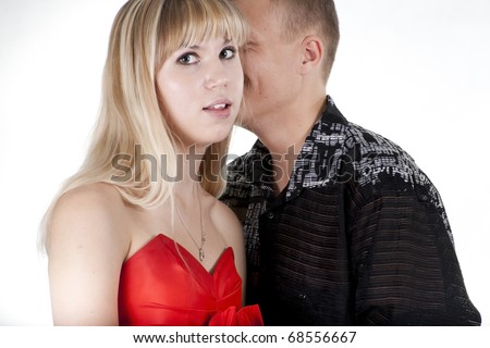 The young man whispers something to the blonde girl
