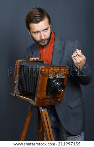 the young man with a beard taking photos with vintage camera - stock photo