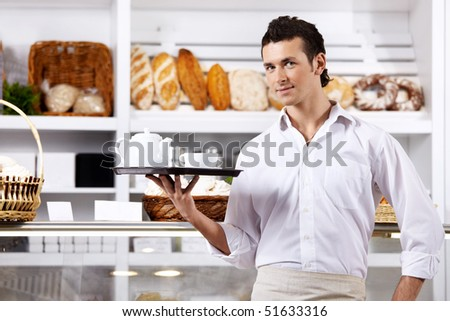The young man with a tray against a show-window - stock photo